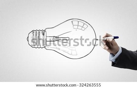 Close up of businessman drawing idea light bulb - stock photo