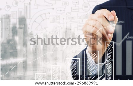 Close up of businessman drawing increasing graph with marker on media screen