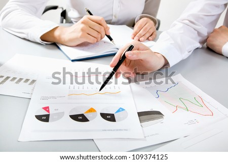 Close-up of businessman explaining a financial plan to colleagues at meeting - stock photo