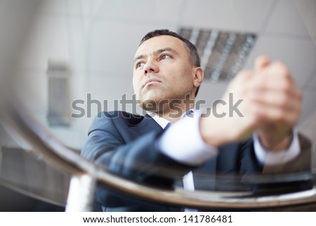 Close-up of businessman face viewed through glass table - stock photo