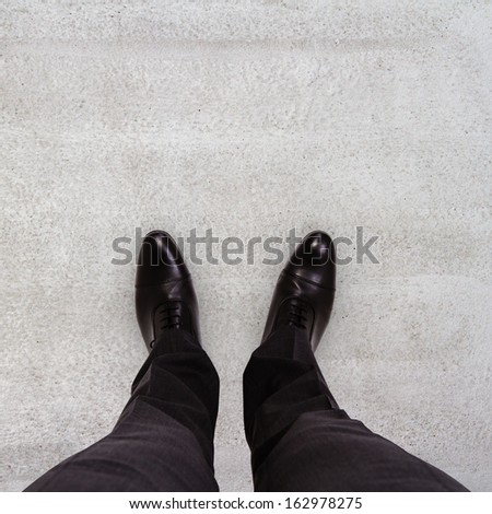 Close-up of businessman feet in black boots on the floor - stock photo