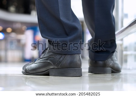 Close-up of businessman feet in black shoes on the floor - stock photo
