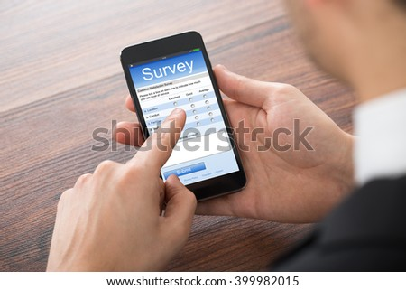 Close-up Of Businessman Filling Online Survey On Mobile Phone - stock photo