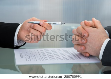 Close-up Of Businessman Giving The Pen To Sign A Contract - stock photo