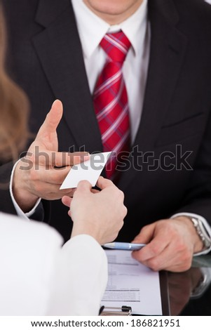 Close-up of businessman giving visiting card to female colleague at desk in office