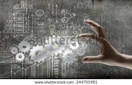 Close up of businessman hand and cogwheel mechanism - stock photo