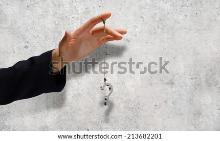 Close up of businessman hand and question sign hanging on finger - stock photo