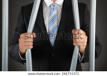 Close-up Of Businessman Hand Bending Bars Of Jail - stock photo
