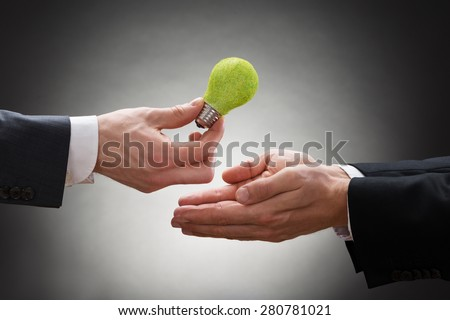 Close-up Of Businessman Hand Giving Eco Light Bulb To Other Businessperson - stock photo