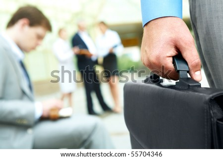 Close-up of businessman hand holding briefcase in working environment - stock photo