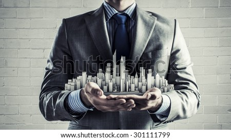 Close up of businessman hand holding construction model - stock photo