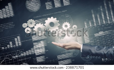 Close up of businessman hand holding gears in palm - stock photo