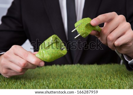 Close-up Of Businessman Hand Holding Grass Covered Electric Plug And Socket - stock photo
