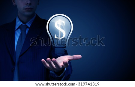 Close up of businessman hand holding money light bulb