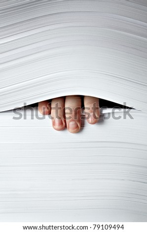 close up of businessman hand in stack of papers - stock photo