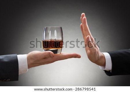 Close-up Of Businessman Hand Reject A Glass Of Whisky Offered By Businessperson - stock photo