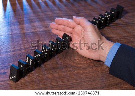 Close-up Of Businessman Hand Stopping Dominoes Falling On Wooden Desk - stock photo