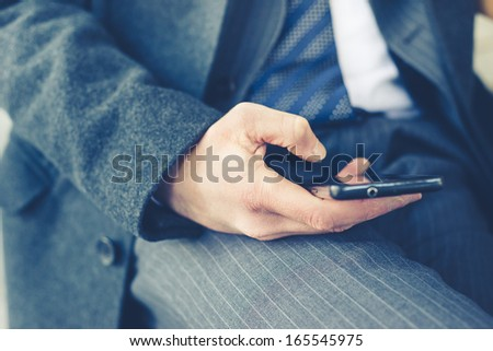 close up of businessman hand typing on smart phone - stock photo