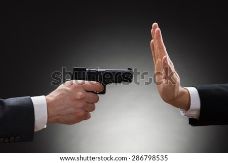 Close-up Of Businessman Hand With Gun Pointing Towards Businessperson Gesturing Stop Sign - stock photo