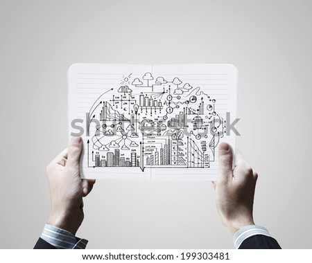 Close up of businessman hands holding opened notepad with sketches - stock photo