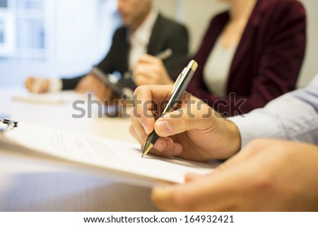 Close-up of Businessman hands making notes during a meeting - stock photo