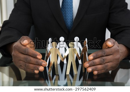 Close-up Of Businessman Hands Protecting Paper Cutout People At Desk - stock photo