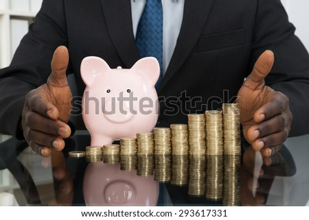 Close-up Of Businessman Hands Protecting Piggybank With Stack Of Coins At Desk - stock photo