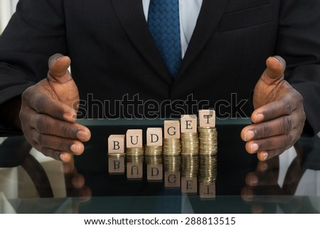 Close-up Of Businessman Hands Saving The Word Budget On Stack Of Coins - stock photo