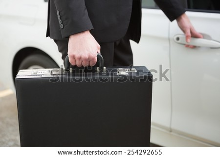 Close up of businessman holding a car door handles in a car park - stock photo