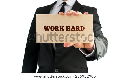 Close up of businessman holding a wooden sign saying Work hard. Isolated on white background. - stock photo
