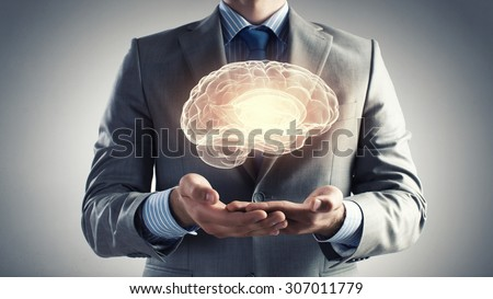 Close up of businessman holding digital image of brain in palm - stock photo