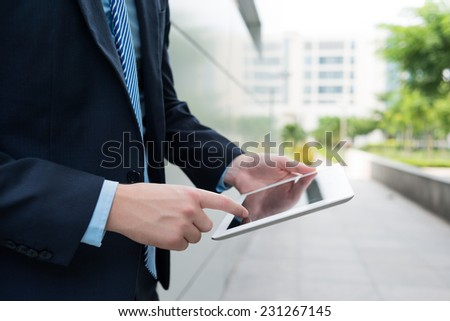 Close-up of businessman holding digital tablet - stock photo