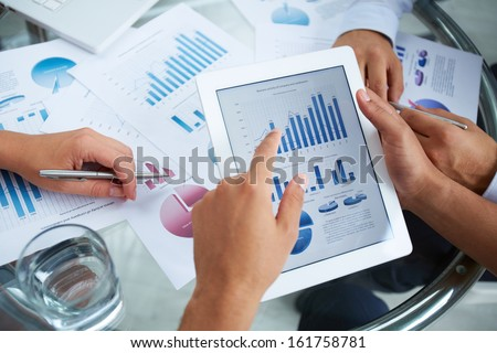 Close-up of businessman holding electronic document in touchpad and pointing at it - stock photo