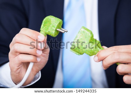 Close-up Of Businessman Holding Grass Covered Electric Plug And Socket - stock photo