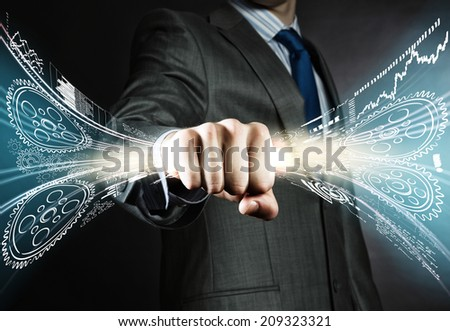 Close up of businessman holding hologram of cogwheels in fist