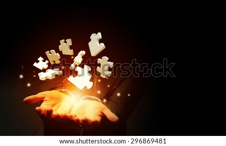 Close up of businessman holding jigsaw elements in palm - stock photo