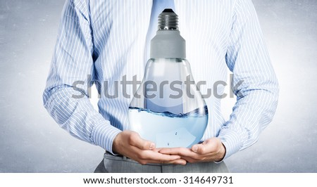 Close up of businessman holding light bulb filled with water