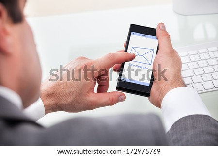 Close-up Of Businessman Holding Mobile With New Message On A Screen - stock photo