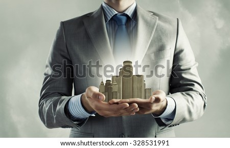 Close up of businessman holding modern office center model in hands - stock photo