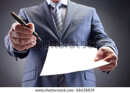 Close-up of businessman holding paper and pen and giving them for signature - stock photo
