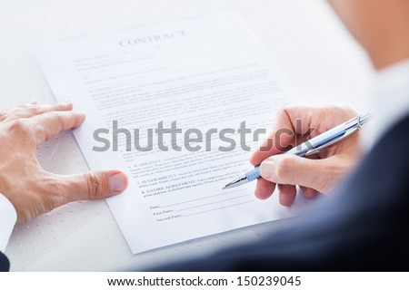 Close-up Of Businessman Holding Pen To Sign On Contract Paper - stock photo