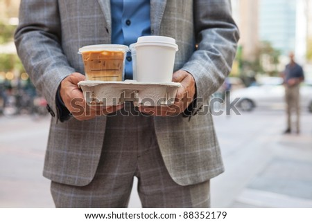 Close-up of businessman holding takeaway coffee cups - stock photo
