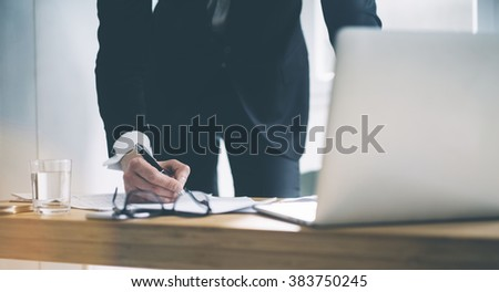 Close up of businessman in black suit working at office and signing documents. Manager standing at his workplace, using laptop and glasses, glass of water
