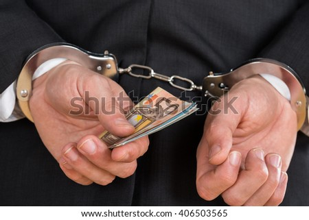 Close-up Of Businessman In Handcuffs Arrested For Bribe - stock photo