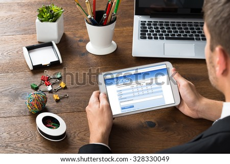 Close-up Of Businessman Looking At Survey Form On Mobile Phone With Office Supplies At Desk - stock photo