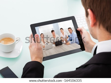 Close-up Of Businessman Looking At Video Conference On Digital Tablet - stock photo