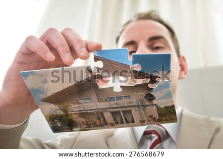 Close-up Of Businessman Making The House Of Puzzle - stock photo