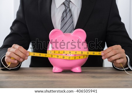 Close-up Of Businessman Measuring Piggybank With Measure Tape At Wooden Desk - stock photo