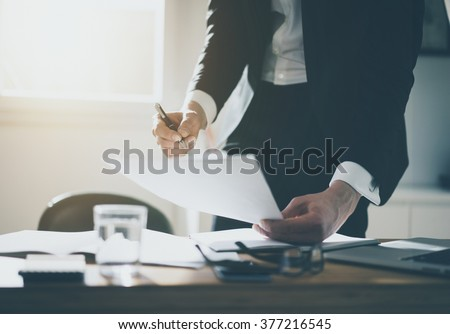 Close up of businessman or lawyer accountant signing documents at desk in office wearing black suite and white shirt - stock photo