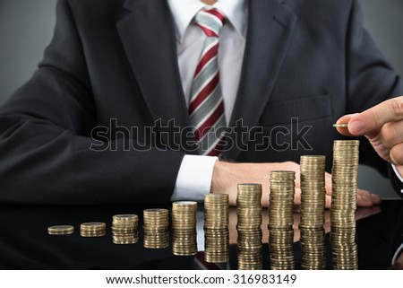 Close-up Of Businessman Placing Coin Over Stack Of Coins At Desk - stock photo